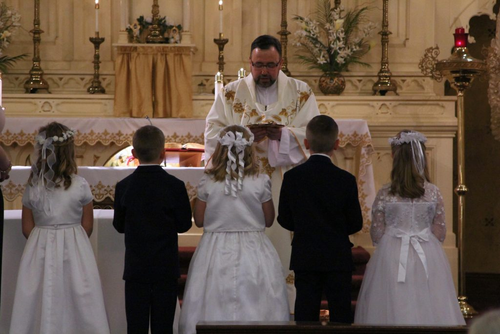 First Communion Children receive blessing on the Altar