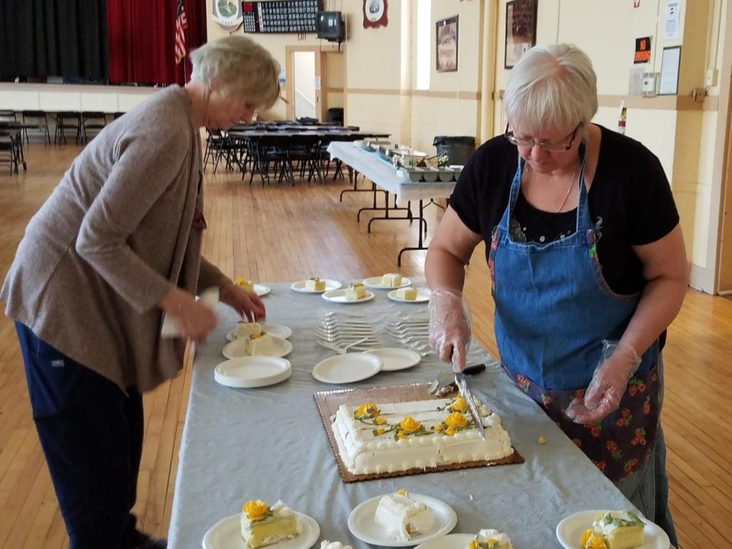 Kathy and Laura cutting cake at 2019 Senior Luncheon